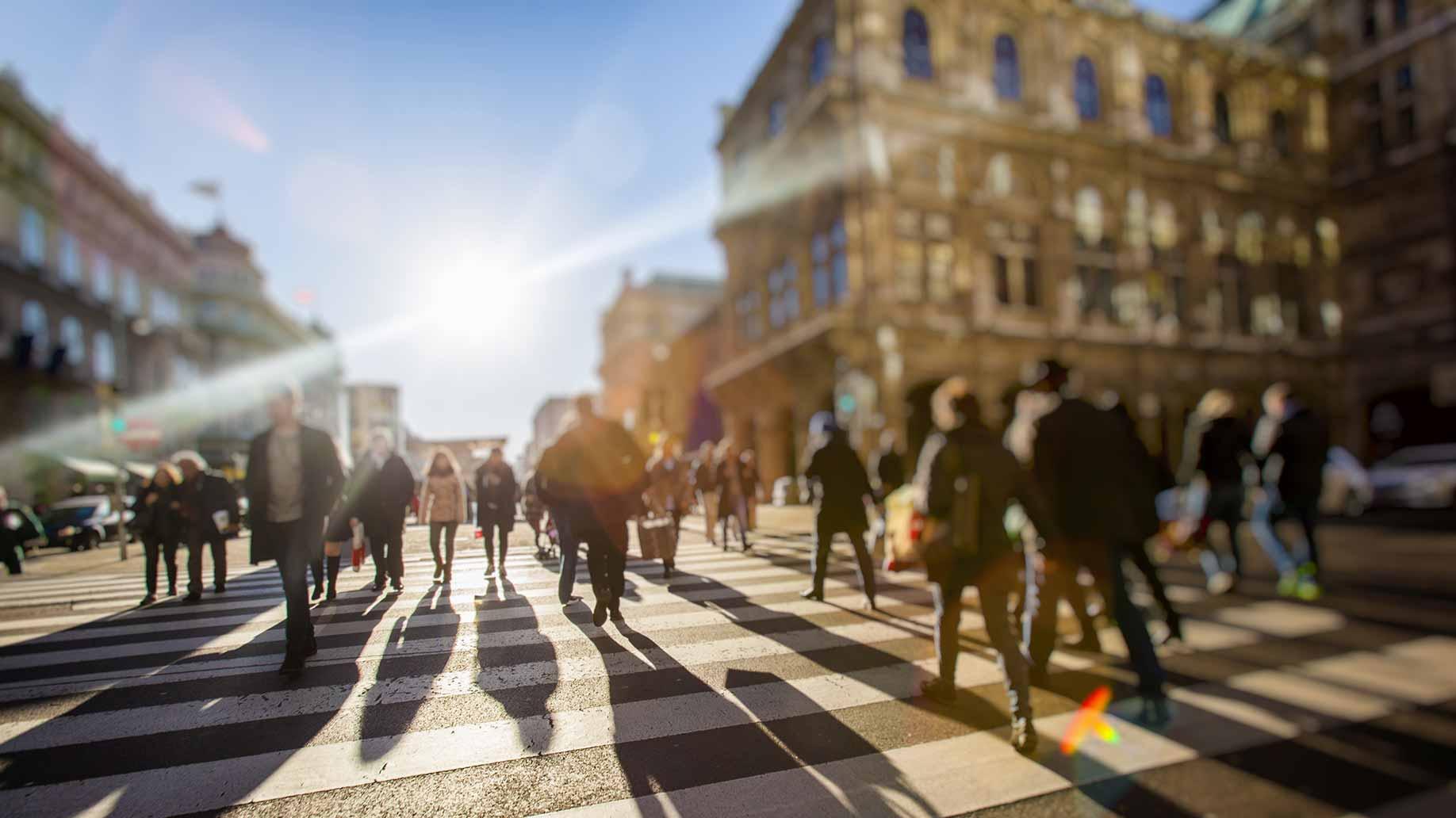 anonymous people walking street golden hour