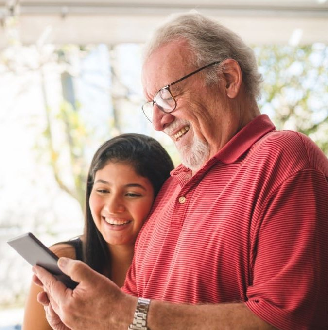 grandpa shows photos on his cell phone for his granddaughter picture id1141804282 e1573758920167